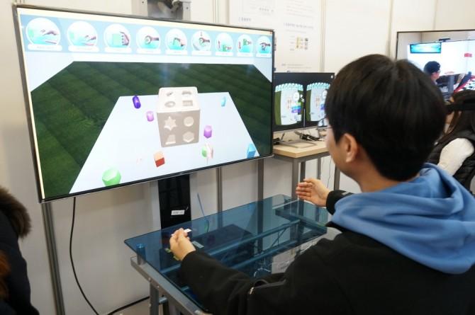 KIST 박정민 박사 연구팀이 개발한 가상물체 조작 기술을 활용해 만든 큐브 게임을 체험 중이다. - 이혜림 기자 제공